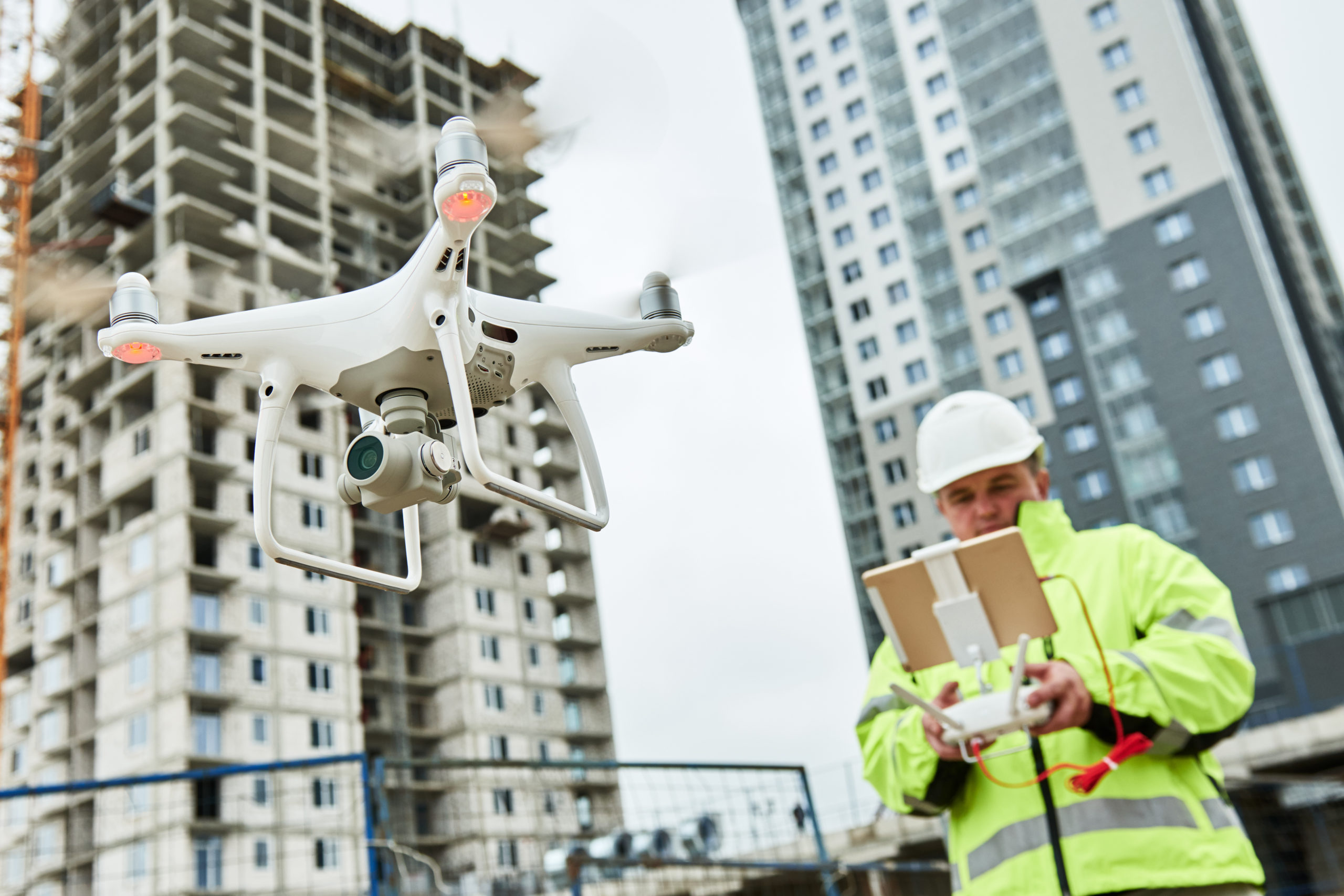 A man in a high-visibility jacket and hardhat flies a quadcopter.